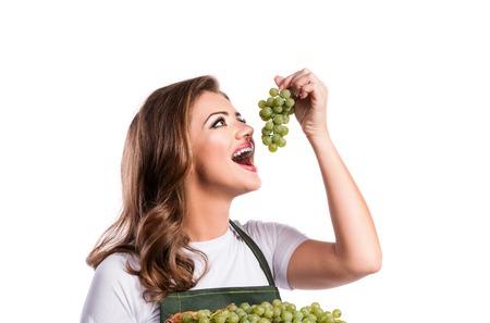 niña comiendo: Joven y bella mujer en el delantal verde. Foto de estudio sobre fondo blanco.
