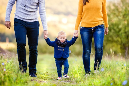 women in jeans: Happy young family spending time together outside in green nature