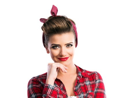 ear checked: Beautiful young woman with pin-up make-up and hairstyle. Studio shot on white background Stock Photo