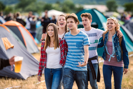 coming together: Beautiful young friends at summer tent festival