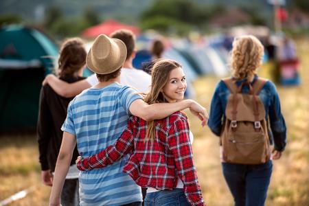 Красивые молодые друзья на фестивале летнего палаточного