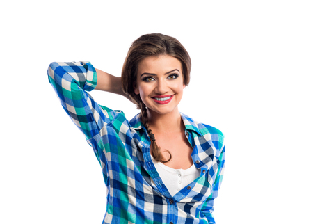blue shirt: Woman with plait in blue and green checked shirt smiling. Studio shot on white background.