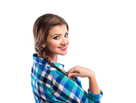 white back: Woman with plait in blue and green checked shirt smiling. Studio shot on white background.