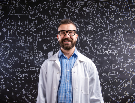 university text: Close up of hipster teacher in white coat and eyeglasses against big blackboard with mathematical symbols and formulas. Studio shot on black background. Stock Photo