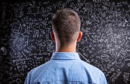 mathematic: Back view of hipster teacher standing against big blackboard with mathematical symbols and formulas. Studio shot on black background. Stock Photo