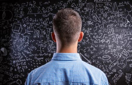 Vista posteriore di insegnante pantaloni a vita bassa in piedi contro grande lavagna con i simboli e le formule matematiche. Studio girato su sfondo nero.
