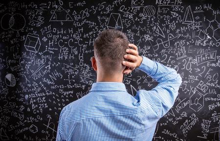 Vista posterior del profesor inconformista de pie contra el gran pizarra con símbolos y fórmulas matemáticas. Foto de estudio sobre fondo negro. Foto de archivo - 51994138