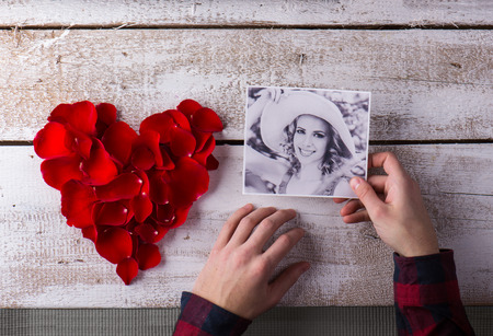 Hands of a man holding photo of his girlfriend. Red rose petal heart. Valentines day composition. Stock Photo - 51994154