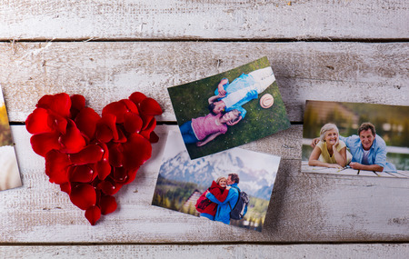 rose photo: Photos of a romantic senior couple laid on white wooden table. Red rose petal heart. Valentines day composition. Stock Photo