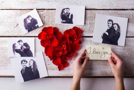 love image: Man holding I love you note. His and his girlfriends photo. Red rose petal heart. Valentines day composition.