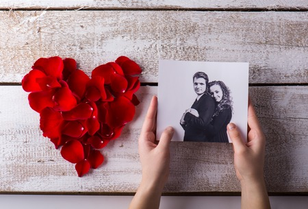 Man holding his and his girlfriends photo. Red rose petal heart. Valentines day composition.