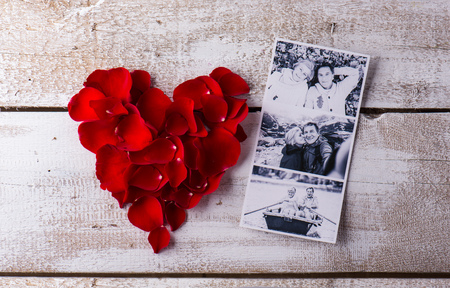 romantic man: Black and white photos of a romantic senior couple laid on white wooden table. Red rose petal heart. Valentines day composition.