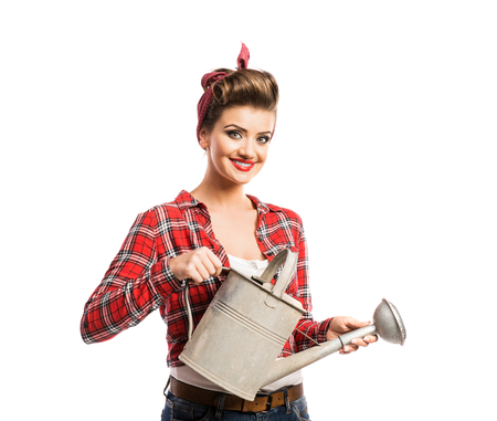 Woman in red checked shirt with pin-up make-up and hairstyle holding metal watering can. Studio shot on white background Zdjęcie Seryjne