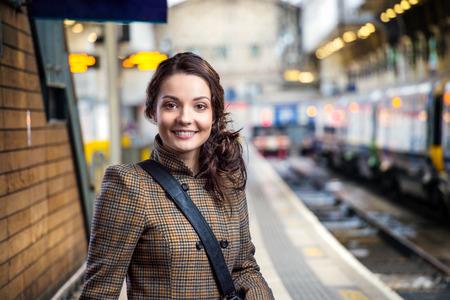 Mujer joven en abrigo de invierno marrón comprobado que espera en la estación de tren