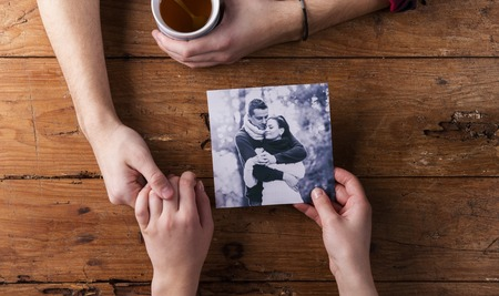 hand holding: Unrecognizable man holding womans hand. Looking  at their photo. Couple in love. Valentines day composition. Studio shot on brown wooden background. Stock Photo