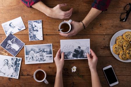 Onherkenbaar mans en dames hand. Kijkend naar hun zwart-wit foto's. Paar in liefde. Koekjes en thee, madeliefje bloem, smart phone. Valentijnsdag samenstelling. Studio opname op bruine houten achtergrond.