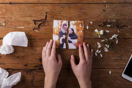 romantic picture: Unrecognizable woman holding torn picture of couple in love. Ended relationship. Crying.Valentines day composition. Studio shot on brown wooden background. Stock Photo