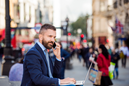busy beard: Hipster manager sitting on stairs on sunny Piccadilly Circus, London, working on laptop, using a smart phone