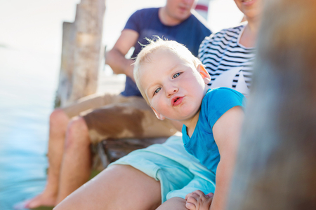 blue shirt: Cute little boy with his parents sitting on the pier on sunny summer day