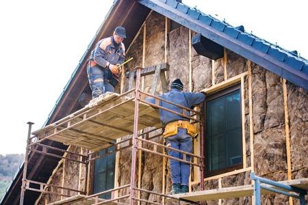 Robotnicy budowlani stojący na rusztowaniu termoizolacyjnym fasadzie domu z wełny szklanej.