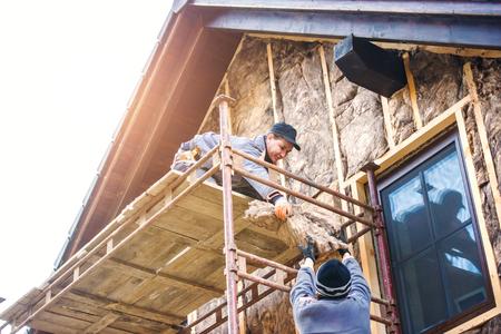 Travailleurs de la construction debout sur échafaudage thermiquement isolante façade de la maison avec de la laine de verre.