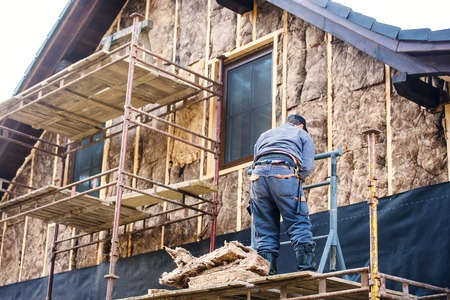 wools: Construction worker standing on scaffold thermally insulating house facade with glass wool.