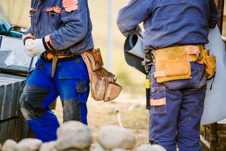 サイト上のツールのバッグと 2 つの建設労働者のクローズ アップ 写真素材