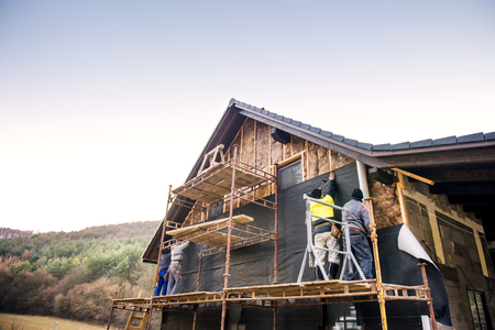 rockwool: Construction workers standing on scaffold thermally insulating house facade with glass wool and black foil.