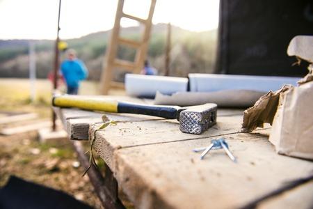 Close-up van de hamer met spijkers op houten planken buiten op bouwplaats Stockfoto