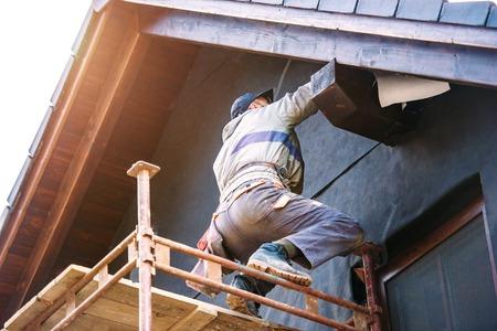 Строитель стоя на эшафоте теплоизолирующий фасад дома стекловатой и черной фольгой.