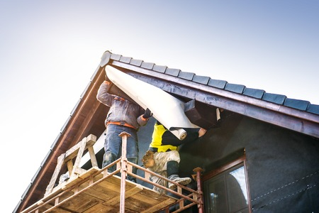 Construction workers standing on scaffold thermally insulating house facade with glass wool and foil.