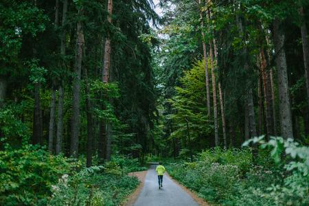 Homem que funciona e que exercita para a fuga funciona em um trajeto na floresta verde velha.
