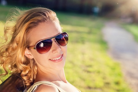attractive female: Beautiful young woman wearing sunglasses outside in sunny summer nature