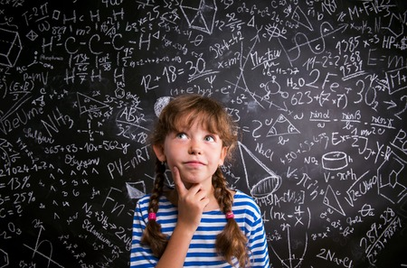 Thinking girl  in blue striped t-shirt with two braids with finger on her cheek against big blackboard with mathematical symbols and formulas Фото со стока