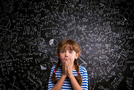 数学記号や数式を使って大きな黒板に対して両手で彼女の口を覆っている青いストライプ t シャツに驚く女の子 写真素材