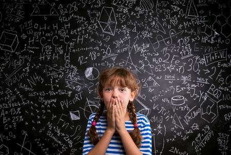 Surprised girl en t-shirt rayé bleu couvrant sa bouche avec les deux mains contre le grand tableau noir avec des symboles et des formules mathématiques
