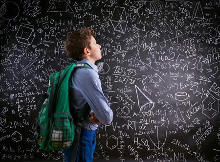 rucksack ': Boy  with schoolbag against big blackboard with mathematical symbols and formulas