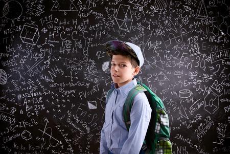 niño con mochila: El muchacho con la cartera contra el gran pizarra con símbolos y fórmulas matemáticas