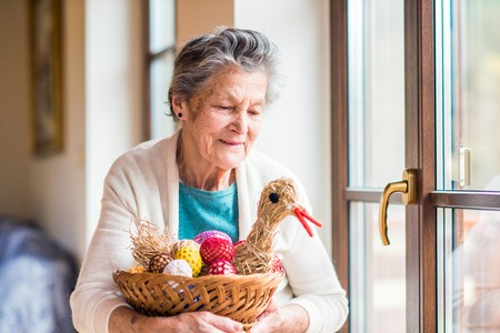 a house with a straw: Senior woman at the window in her house holding basket with Easter eggs and straw hen Stock Photo