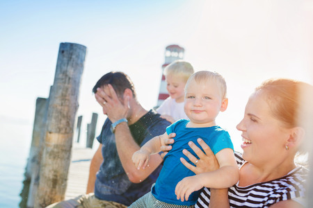 wet t shirt: Family with two sons sitting on the pier at the lighthouse on sunny summer day