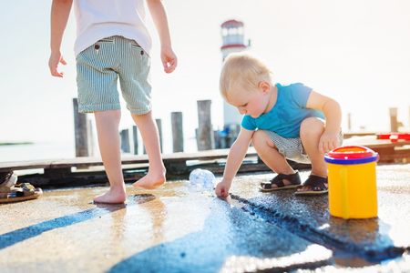 wet t shirt: Two boys playing on the pier at the lighthouse on sunny summer day Stock Photo