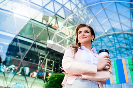 business center: Close up of smiling elegant businesswoman holding thermo coffee cup in pink jacket and white shirt against glassy modern office building