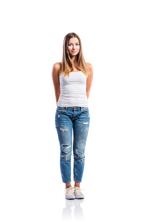 white singlet: Standing teenage girl in jeans, tight singlet and sneakers, hands holding behind back, young woman, isolated on white background