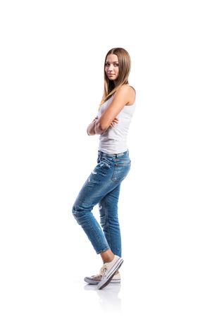 jeans apretados: De pie adolescente en pantalones vaqueros, camiseta y zapatillas de deporte apretado, con los brazos cruzados, mujer joven, aislado en fondo blanco