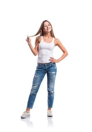 tight jeans: De pie adolescente en jeans, singlete ajustado y zapatillas de deporte, haciendo girar su pelo, mujer joven, aislado en fondo blanco Foto de archivo
