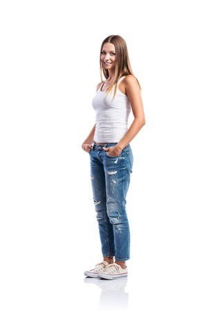 Standing teenage girl in jeans, tight singlet and sneakers, hands in the pockets, young woman, isolated on white background