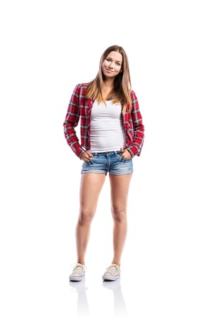 white singlet: Standing teenage girl in denim shorts, tight singlet, red checked shirt and sneakers, hands in the pockets, young woman, isolated on white background