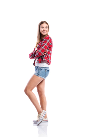 white singlet: Standing teenage girl in denim shorts , tight singlet, red checked shirt and canvas sneakers, arms crossed, young woman, isolated on white background Stock Photo