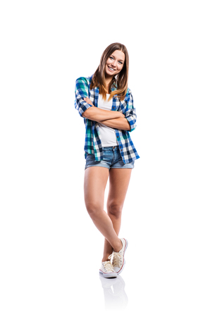 white singlet: Standing teenage girl in denim shorts , tight singlet, blue checked shirt and canvas sneakers, arms crossed, young woman, isolated on white background Stock Photo