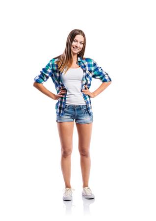 jeans apretados: De pie adolescente en pantalones cortos de mezclilla, singlete apretado, azul camisa a cuadros y zapatillas de deporte de la lona, ??los brazos en las caderas, mujer joven, aislado en fondo blanco